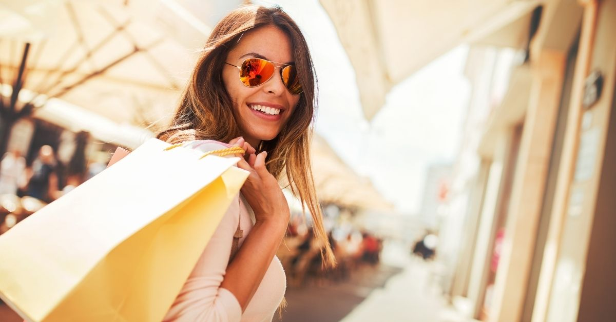 woman with shopping bags and sunglasses smiling