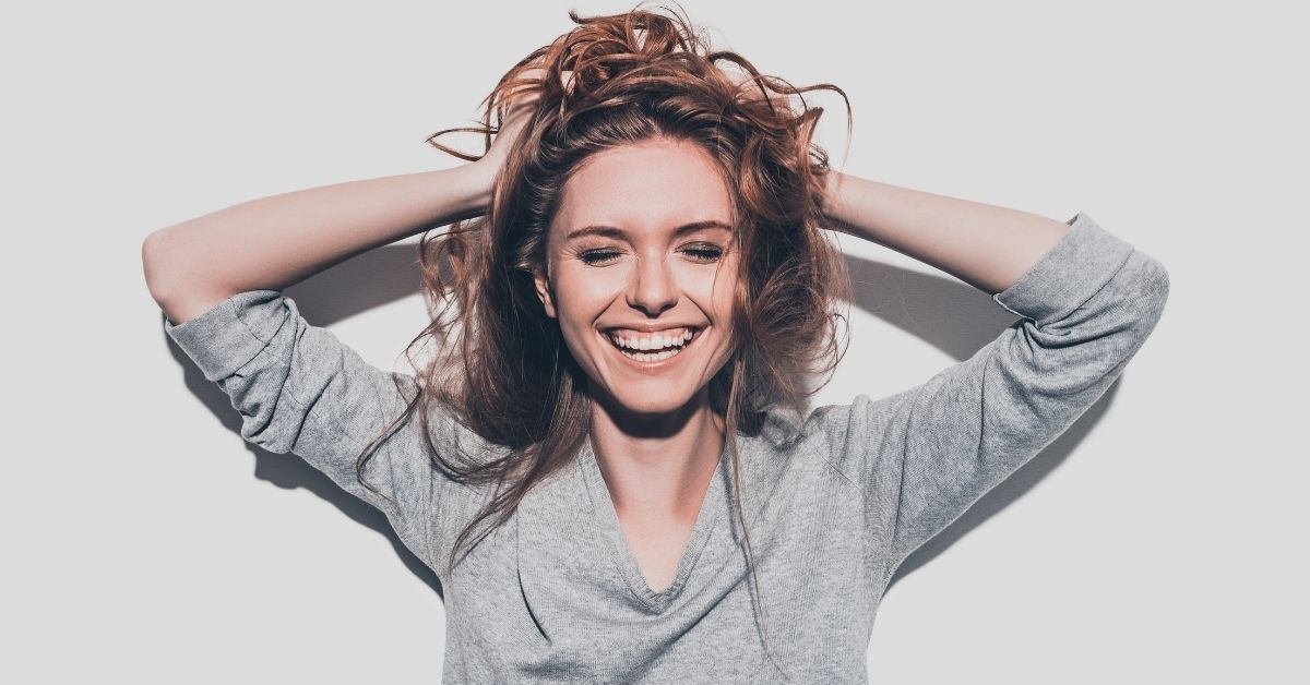 woman smiling with grey jumper on